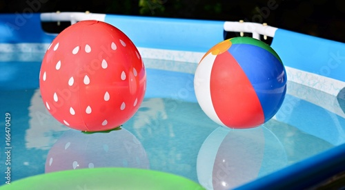 Children playing beach balls floating in swimming pool.