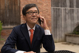Asian businessman talking on a cell phone - 166474881