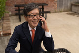 Asian businessman talking on a cell phone - 166474885