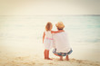 father and little daughter hug on beach - 166476066