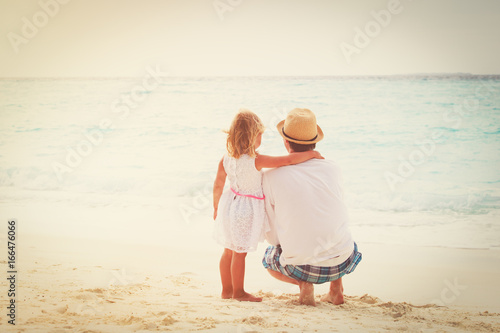 father and little daughter hug on beach