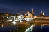 Evening photo of illuminated bridge and St. John the Baptist Cathedral in Wroclaw, Poland