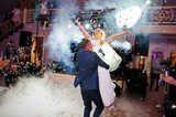 Newly married couple dancing on their wedding party with heavy smoke and multicolored lights on the background. - 166482096