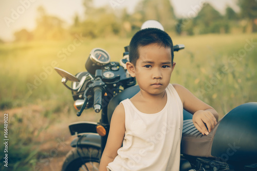 Little kid  on classic motocycle in park. Poster