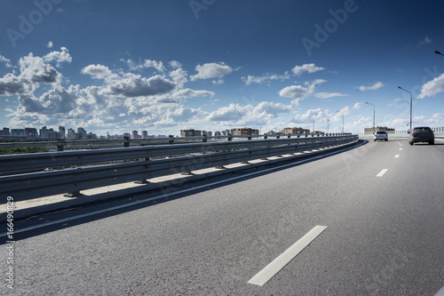 Asphalt road with metal barrier under the Sun © Mak