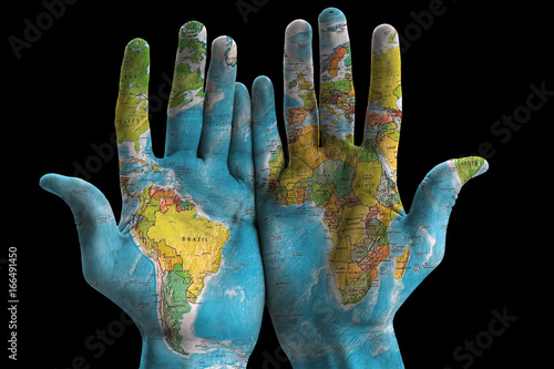 Map of the world painted on hands, isolated on black