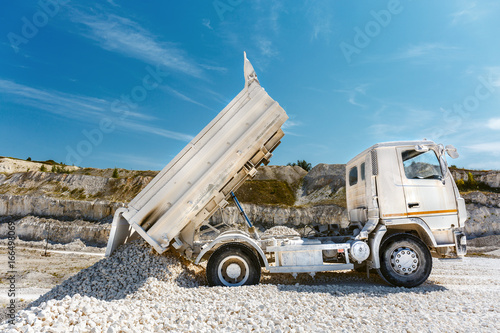 Foto op Canvas Blauw Process of mining of limestone in the chalk quarry. White truck unloads the waste production
