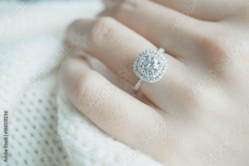 Zamyka w górę Diamentowego pierścionku na kobieta palcu przed ślubem z białym szalika tłem (miękka i selekcyjna ostrość)