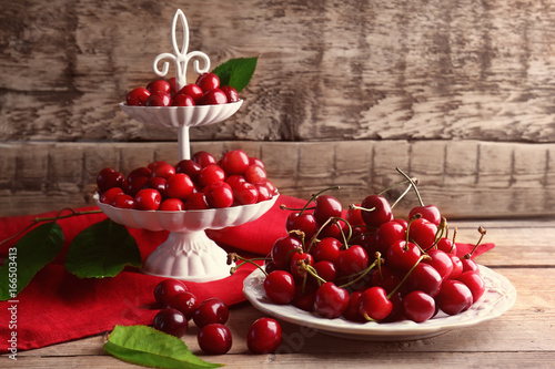 Plate and stand with cherries on wooden background