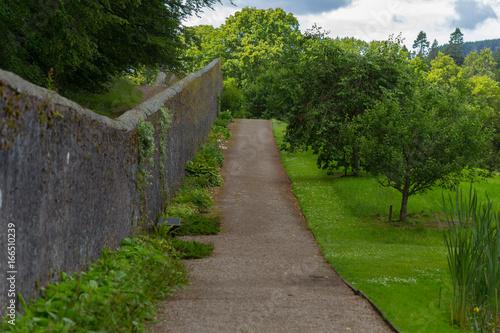 Weg entlang einer Mauer in einem Garten
