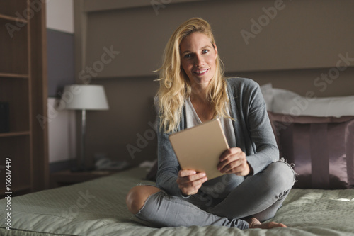 Wall mural Beautiful blond woman relaxing on bed