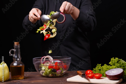 Sticker Chef neatly mixing fresh summer salad in a bowl. Cooking process, restaurant concept