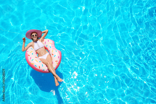 Beautiful young woman with inflatable donut in blue swimming pool