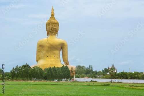 Golden Buddha in countryside. Large Buddha statue at Wat Muang in Angthong in back side rural landscape in Thailand.