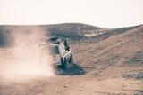 Jeep bashing through dusty sand dunes in desert