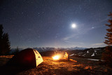 Male hiker have a rest in his camp near the forest at night. Man sitting near campfire and tent under beautiful night sky full of stars and the moon, and enjoying night scene in the mountains