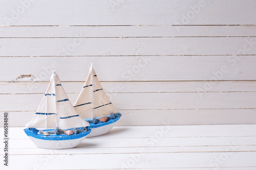 Foto op Aluminium Zeilen Decorative wooden toys sailing boats on white wooden background.