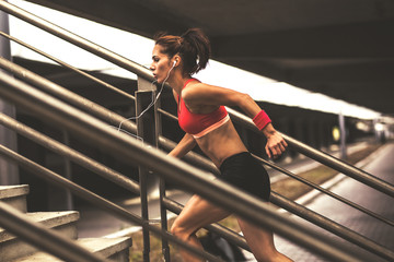 Female runner jogging on the city street.She runs up the stairs.City environment.