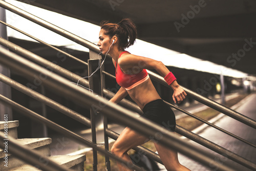 Female runner jogging on the city street.She runs up the stairs.City environment. - 166593651