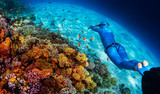 Woman freediver glides over vivid coral reef in a crystal clear tropical sea