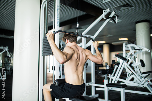 Poster Brutal athletic man pumping up muscles on crossover. Muscular man working out in gym doing exercises . gym