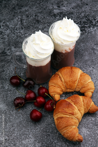 Wall mural Iced coffee with whipped cream in tall glass and fresh croissant