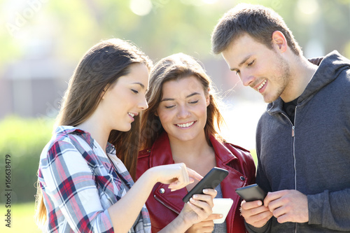 Three friends sharing on line content in the street
