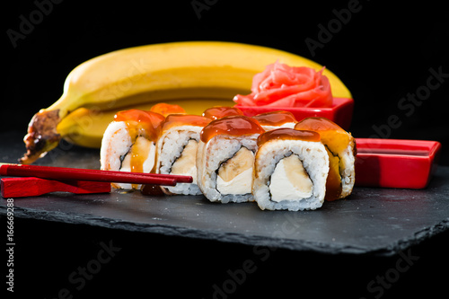 Traditional Japanese cuisine. Sweet sushi rolls with salmon, cream cheese, rice and banana was poured with jam on dark background, selective focus
