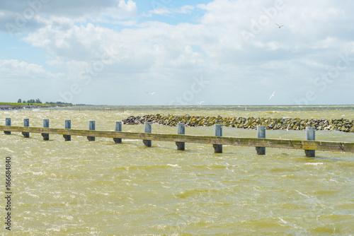 Foto op Aluminium Pier Shoreline of a stormy lake in sunlight in summer