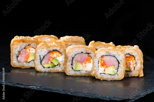 Traditional Japanese cuisine. Selective focus on sushi rolls with salmon, cream cheese, rice, cucumber, caviar and raw meat on dark background