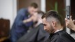 Close up of bearded man sitting with black cutting cape in barbershop. Female barber is making perfect shape for haircut using electric trimmer. Male hairstylist working with client in the background.