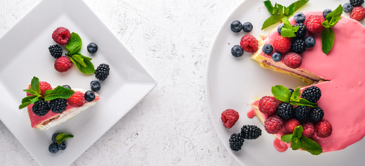 Cake with butter and fresh berries and fruits. Dessert. On a wooden background. Top view. Free space for your text.