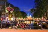 Amsterdam at night, with flowers and bicycles on the bridge, Holland, Netherlands.