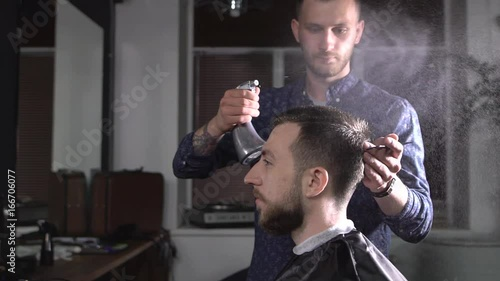 Image of stylish male barber spraying water on hair of client and brushing it to make stylish haircut. Young hairdresser working at the barbershop doing undercut with comb and styling products.
