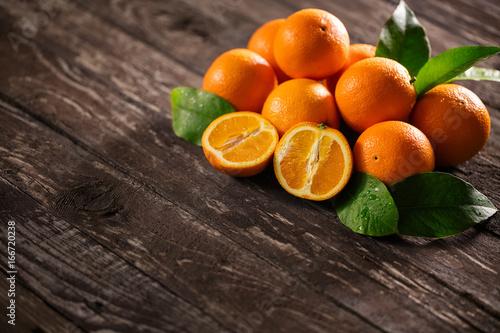 Freshly harvested orange on wooden background.