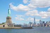 Statue of Liberty island and New York city skyline in a sunny day, white clouds - 166725872