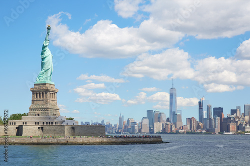 Foto op Aluminium New York Statue of Liberty island and New York city skyline in a sunny day, white clouds