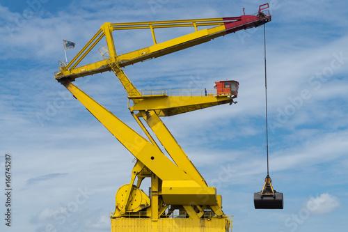 gelber Hafenkran mit Schaufel vor blauem Himmel