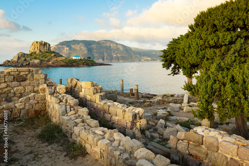 Ancient ruins and small island Kastri with traditional orthodox church in Kefalos bay in Kos island, Greece.
