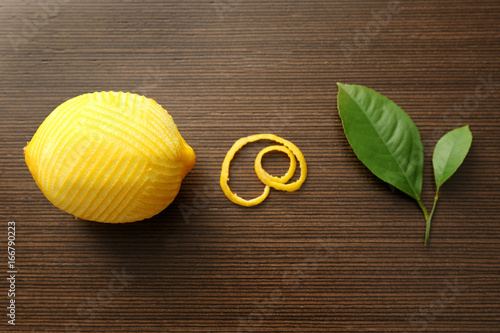 Fresh peeled lemon, zest and leaves on wooden table