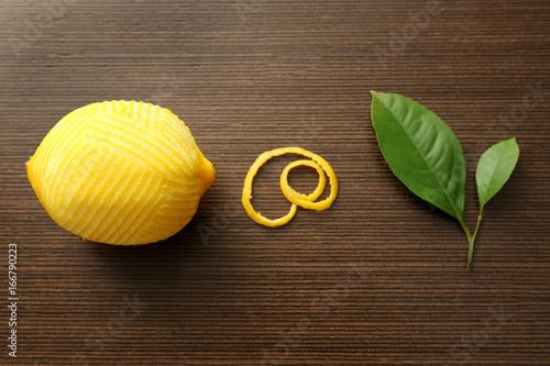 Fresh peeled lemon, zest and leaves on wooden table