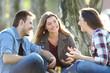 Three friends talking sitting in a park