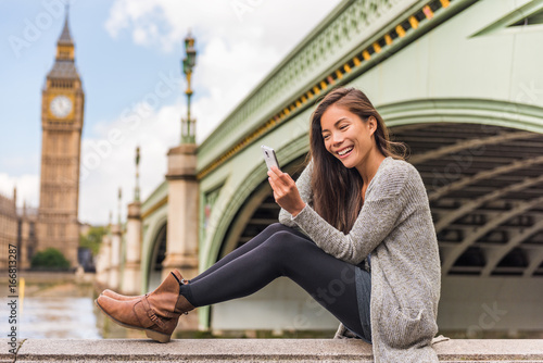 London urban people city lifestyle woman using phone app texting sms on social media. Young Asian girl holding cellphone at Westminster bridge, Big Ben Houses of Parliament background.