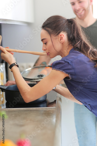 Couple cooking together in their kitchen at home - 166841081