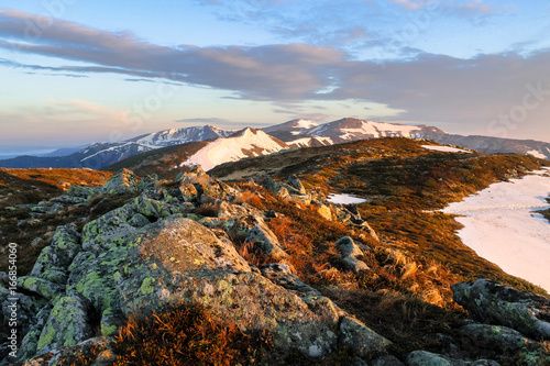 typical mountain landscape with stones rock in the foreground on the way snow covered valley at sunrise nature hiking