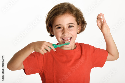 Little girl brushing her teeth with a toothbrush. Poster