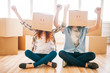 Playful couple with boxes on heads, housewarming
