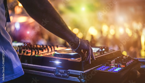 Dj mixing outdoor at beach party festival with crowd of people in background - Summer nightlife view of disco club outside - Soft focus on hand - Fun ,youth,entertainment and fest concept - 166872827