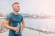Portrait of healthy athletic middle aged man with fit body holding bottle of refreshing water, resting after workout or running. on the riverside. vintage color
