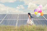 A funny girl carrying a colorful balloon running in a meadow with a Solar panel, photovoltaic. Concept of Eco-Friendly ,Clean Energy , Pure energy and Sustainable energy - 166890288